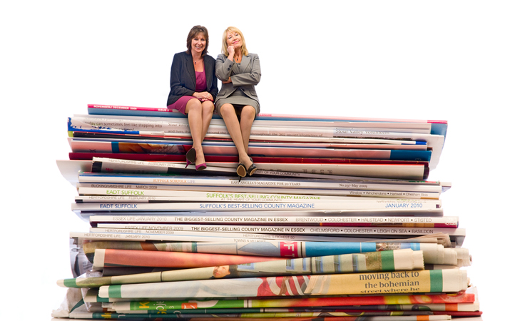 copywriters sitting on giant magazines